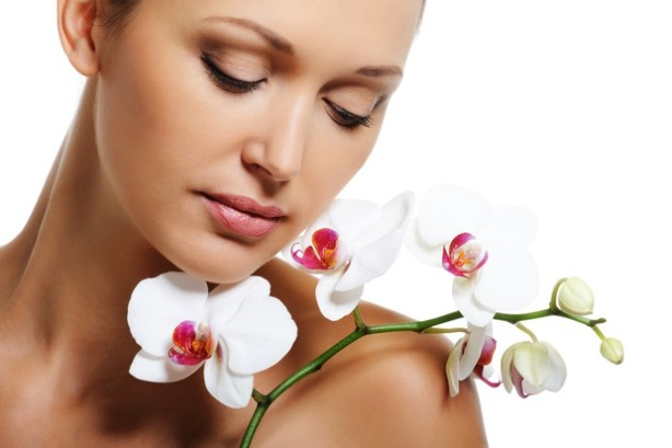 Face of pretty beautiful woman with a white orchid on her shoulder